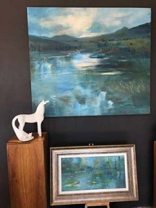 Carol Hayward-Fell's ceramic horse talks to large format Oil on canvas painting by artist Diane Erasmus titled 'Blue Waters'. Framed canvas below also by Diane Erasmus is titled 'Water Lillies'.
